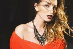 一个美丽的年轻性感的女孩的画象一片红色礼服和红色嘴唇的 免版税图库摄影