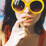 一个美丽的年轻性感的深色的女孩的画象有传神眼睛的和充分的摆在为照相机的嘴唇和太阳镜 图库摄影