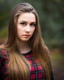 一个美丽的黑暗的白肤金发的十几岁的女孩的画象在森林里 免版税库存照片