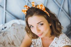 一个美丽的年轻甜女孩的画象有迷人的微笑和垫铁的在微笑的长颈鹿的头摆在和 免版税库存图片