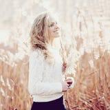 一个美丽的年轻白肤金发的女孩的画象一个领域的在白色套头衫,微笑,概念秀丽和健康 免版税图库摄影