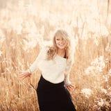 一个美丽的年轻白肤金发的女孩的画象一个领域的在白色套头衫,秀丽的微笑,概念和健康 免版税库存图片