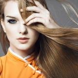一个美丽的年轻白肤金发的女孩的画象在灰色背景的与开发的头发,秀丽的概念演播室 免版税库存图片
