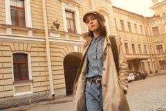 一个美丽的年轻行家女孩的画象通过街道走老镇乐趣和微笑 免版税图库摄影