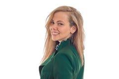 一个美丽的年轻金发碧眼的女人的画象站立平直斜向一边的看起来和微笑的一件高尔夫球外套的 库存图片
