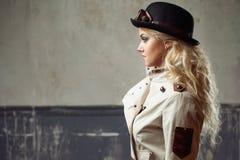 一个美丽的steampunk妇女帽子常礼帽帽子的画象在难看的东西背景的 库存照片