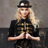 一个美丽的steampunk妇女帽子常礼帽帽子的画象在难看的东西背景的 图库摄影