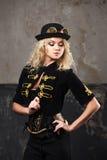 一个美丽的steampunk妇女帽子常礼帽帽子的画象在难看的东西背景的 库存图片