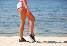一个美丽,肌肉女运动员在她的手上拿着红色绳索,被转动她  免版税库存图片