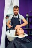 一个美发师人洗涤头发头给椅子的b客户 库存照片