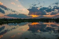 一个美好的夏天晚上 剧烈的日落在一个河或湖的水中反射城市郊外的 库存图片