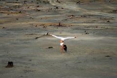 一个美好的姿势的灵活的体操运动员女孩在启示风景背景在沙漠 库存照片