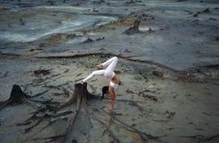 一个美好的姿势的灵活的体操运动员女孩在启示风景背景在沙漠 免版税库存图片