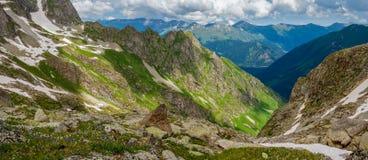 一个美好的山风景的全景与绿色倾斜和雪的 图库摄影