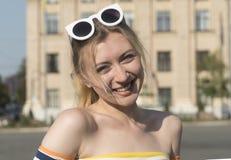 一个美好的年轻人微笑白肤金发的女孩的画象在一条城市街道在一个晴天, smilling的女孩上的 库存照片
