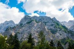 一个美好的风景在山、云彩在峰顶上和森林前景的 免版税库存照片
