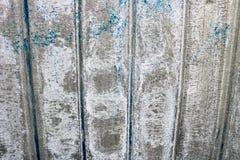 一个美妙地被绘的金属表面的明亮的灰色饱和的安心纹理与垂直条纹和破旧的削皮油漆的 库存照片