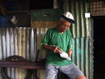 一个老亚裔人演奏纵横填字游戏 免版税库存照片