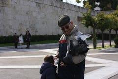一个老人和一只男孩哺养的鸽子在结构体squareï ¼ Œgreece 库存图片