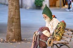 一个老人背包徒步旅行者坐一条方形的长凳,在笔记薄佩带的镜片和地精羊毛帽子写下笔记 免版税图库摄影