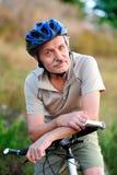 一个老人骑自行车者的特写镜头画象 库存图片