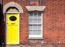 一个老传统英国露台的房子的黄色前门 免版税库存照片