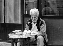一个老哀伤的人坐一块石砖在布加勒斯特市中心附近 库存照片