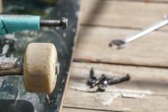 一个老在一张木桌上的滑板轮子说谎的等待的修理的特写镜头在庭院里在一个晴天 免版税库存图片