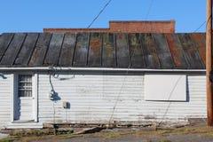 一个老大厦的侧视图与古色金属屋顶和烂掉基础板的 库存图片