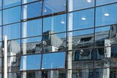 一个老大厦的反射在一个现代玻璃门面的,对比 图库摄影