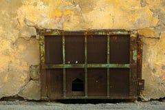 一个老大厦的地下室与用生锈的栅格盖的落的膏药的 与栅格的街道平实窗口块 免版税库存照片