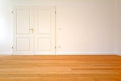 一个老大厦的客厅-与双门和木条地板地板的公寓在整修以后 免版税图库摄影