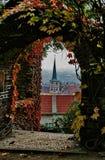 一个老大厦的看法与一个尖顶的通过与色的秋叶的曲拱, Praga 免版税库存照片