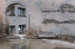 一个老大厦,与窗口的曲拱的被破坏的墙壁,在前景与池水的石表面 库存照片