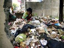 一个老妇人为在堆的可回收材料寻找或清除在被放弃的全部的垃圾 免版税图库摄影