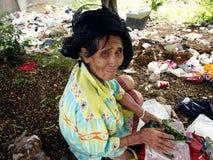 一个老妇人为在堆的可回收材料寻找或清除在被放弃的全部的垃圾 库存图片