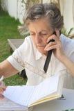 一个老妇人发表演讲关于手机并且采取在她的议程的有些笔记 免版税库存图片