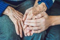 一个老妇人和一个年轻人的手 照料年长的人 C 免版税库存照片