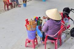 一个老妇人在一座塔卖香火在越南 库存图片