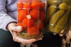一个老妇人在她举行起了皱纹手一个瓶子黄瓜和蕃茄 冬天准备在银行中 免版税库存图片