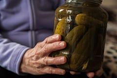 一个老妇人在她举行起了皱纹手一个瓶子黄瓜和蕃茄 冬天准备在银行中 图库摄影
