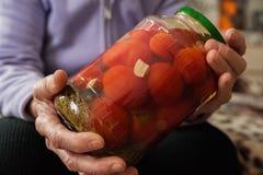 一个老妇人在她举行起了皱纹手一个瓶子黄瓜和蕃茄 冬天准备在银行中 免版税库存照片
