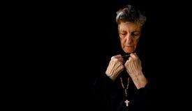 一个老妇人在庭院里祈祷 免版税库存图片