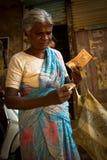 一个老妇人在Dharavi贫民窟计数她的金钱在孟买Indi 免版税图库摄影