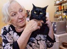 一个老妇人拥抱她的猫 免版税库存图片