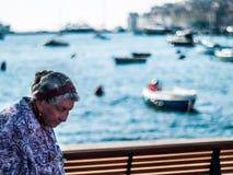 一个老妇人的创造性的场面从罗维尼,克罗地亚欧洲中部的午间,与美丽的小船bokeh球有用为样品 免版税图库摄影