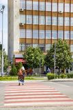 一个老妇人的背面图有一个弯曲处的在红白斑马线在季米特洛夫格勒,保加利亚 库存图片