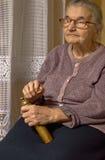 一个老妇人的画象有研磨机的在手上。 库存照片