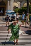 一个老妇人穿过在卡尔顿旅馆,戛纳前面的大道 图库摄影
