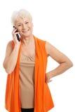 一个老妇人谈话通过电话。 库存图片
